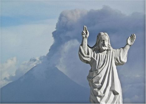 A statue of Jesus Christ on the cemetary of Ambato with ash spewing Tungurahua volcano in the background
